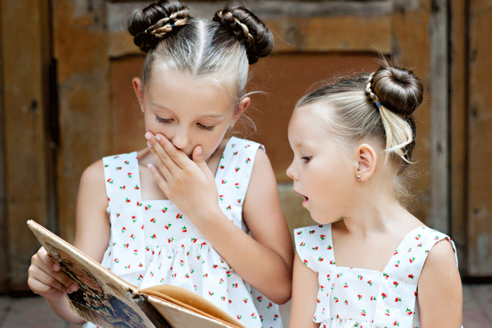 young girls reading outside
